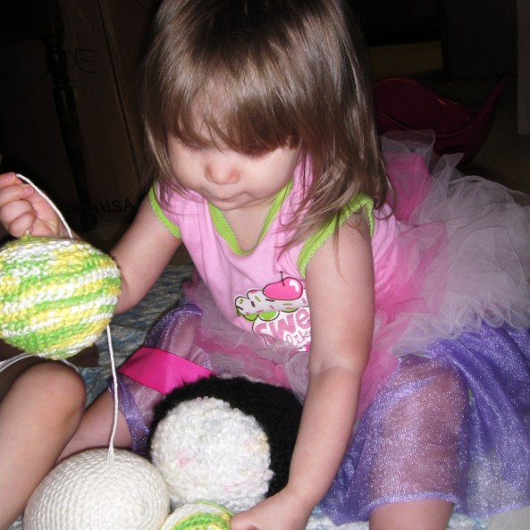 A baby with crochet and knit toys