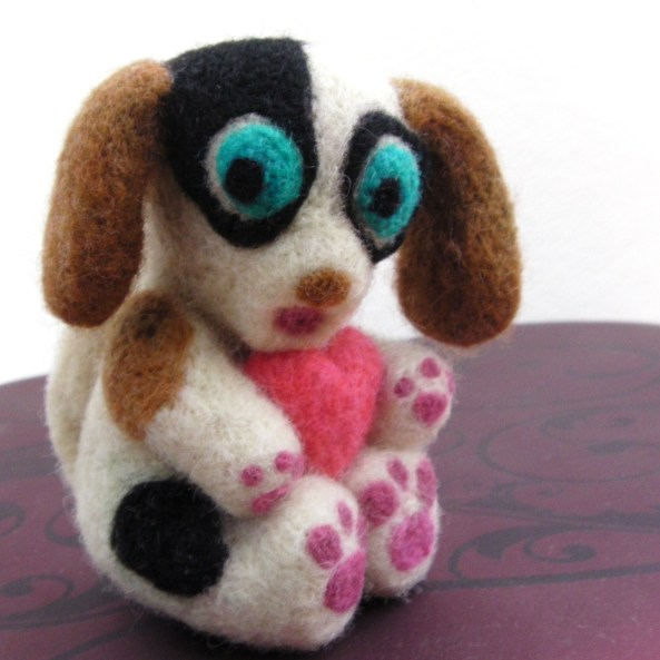 needle felted puppy holding a pink heart
